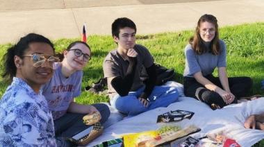 4 students sitting enjoying a picnic and smiling at the camera.